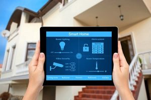 Contact — hands holding tablet with home security app in front of house in Redwood City, CA