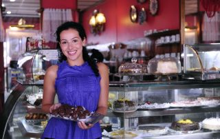 small business owner showing desserts in her shop